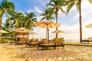 Beautiful luxury umbrellas and chairs around an outdoor swimming pool in hotel and resort with coconut palm trees on sunset or sunrise sky - holiday and vacation concept photo