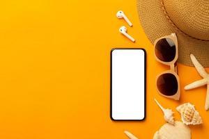 Fondo de verano con teléfono de pantalla en blanco y accesorios de playa, máscara para evitar el covid-19 en la vista superior de fondo naranja vibrante con espacio de copia. foto