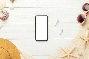 Fondo de verano con accesorios de playa y teléfono de pantalla en blanco sobre fondo de madera blanca vista superior con espacio de copia. foto