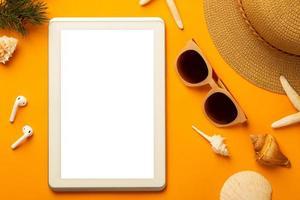 Fondo de verano con tableta de pantalla en blanco y accesorios de playa en vista superior de fondo naranja vibrante con espacio de copia. foto