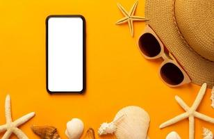 Summer background with blank screen phone and beach accessories, mask to prevent covid-19 on vibrant orange background top view with copy space. photo