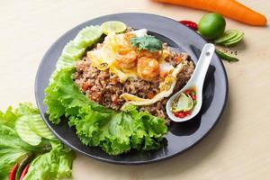 Arroz frito con camarones en plato negro sobre la mesa foto