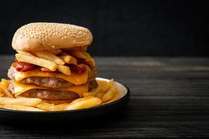 Pork hamburger or pork burger with cheese, bacon, and french fries photo