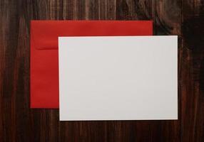 maqueta de tarjeta de felicitación en blanco con sobre rojo foto