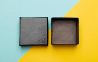 Black box packaging on half blue and yellow background photo