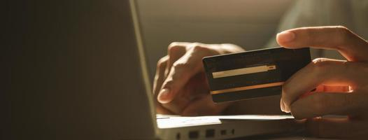 Hand holding credit card and using laptop for online shopping photo