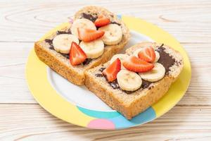 Whole wheat bread toasted with fresh banana, strawberry, and chocolate for breakfast photo