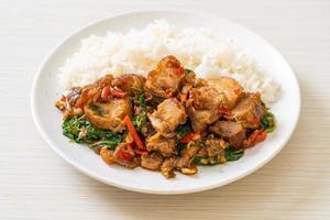 Panceta de cerdo crujiente salteada y albahaca con arroz - estilo de comida callejera local asiática foto