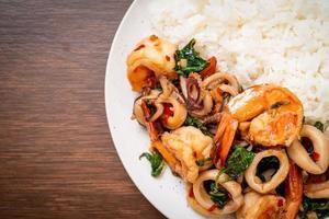 arroz y mariscos salteados de camarones y calamares con albahaca tailandesa - estilo de comida asiática foto