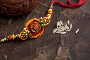 Raksha Bandhan background with an elegant Rakhi and scattered rice. A traditional Indian wrist band which is a symbol of love between Brothers and Sisters. photo