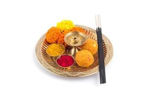 Pooja thali bellamente decorado para la celebración del festival para adorar, haldi o cúrcuma en polvo y kumkum, flores, palos perfumados en placa de latón, puja thali hindú foto