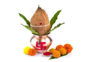 Copper Kalash with coconut, mango leaf, Haldi, kumkum and sweets with marigold flower decoration on a white background. Essential in Hindu puja. photo