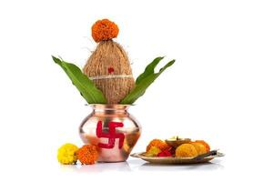 Copper Kalash with coconut and mango leaf and pooja thali with diya, kumkum and sweets with floral decoration on a white background. Essential in hindu puja. photo