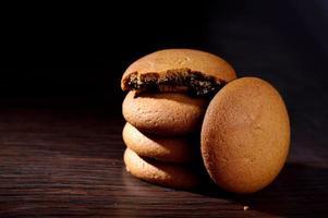galletas rellenas de crema de chocolate. galletas de crema de chocolate. Galletas de chocolate marrón con relleno de crema sobre fondo negro. foto