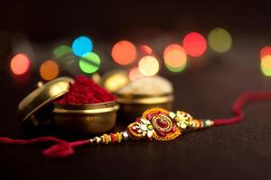 Raksha Bandhan background with an elegant Rakhi, Rice Grains and Kumkum. A traditional Indian wrist band which is a symbol of love between Brothers and Sisters. photo