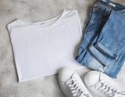 Stylish female clothes set. Woman outfit on concrete background. photo
