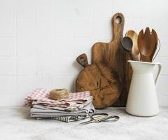 Kitchen utensils, tools and dishware on on the background white tile wall. photo