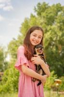 A teenage girl with a Chihuahua dog in her arms on a blurred background of trees is smiling. photo