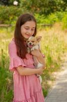 perro chihuahua en los brazos de una niña. un adolescente con un cachorro. foto