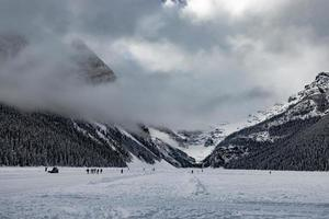 Beehive and Devils Thunb watch over ice skaters with clouds rolling by. Lake Louise. Banff National Park, Alberta, Canada photo