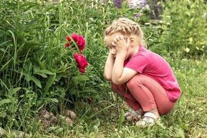 A little girl holding her head in thought, sitting by a flower bed in the garden of pink peonies photo