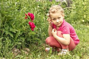 The little girl is lost in thought, sitting by the flower bed in the garden of pink peonies photo