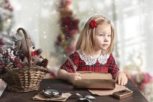 A little girl in a red dress is sitting at the table and writing a letter to Santa. Christmas card photo
