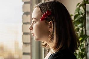 Portrait of a beautiful sad girl looking out the window with hope and expectation. Hairpin with hearts. First love on Valentine's Day photo