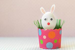White chicken egg with bunny ears and a muzzle in an environmentally friendly pink paper tray, box. Happy Easter holiday concept. photo
