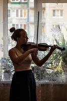 Silhouette of a young girl, a musician. Playing the violin in the background of the window photo