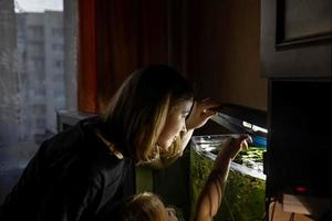 A young woman and a little girl feed fish in a home aquarium photo