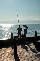 Silhouette of man fishing on the seashore photo