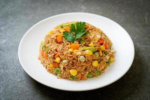arroz frito con guisantes, zanahorias y maíz - estilo de comida vegetariana y saludable foto