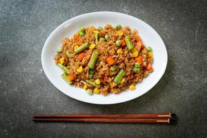 Fried rice with green peas, carrots, and corn - vegetarian and healthy food style photo
