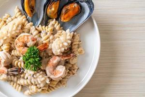 Pasta espiral con salsa de crema de champiñones y mariscos - estilo de comida italiana foto