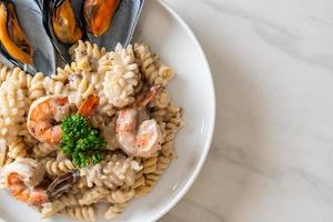 Spiral pasta mushroom cream sauce with seafood - Italian food style photo