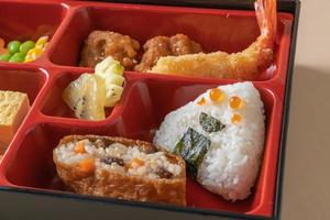 arroz de sushi inari envuelto en tofu seco con camarones fritos y pollo frito en un juego de bento - estilo de comida japonesa foto