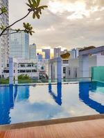 Skyscraper view from swimming infinity pool in Bangkok, Thailand photo