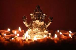 Ganesh idol surrounded with oil lamp photo