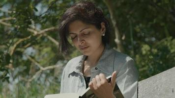 Woman sitting on wooden bench in the country reading a book video