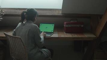 Woman sitting at table typing and scrolling on laptop with green screen video