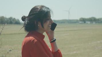femme debout dans le champ appelant avec smartphone video
