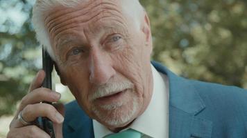 uomo in piedi in un'area verde che chiama con lo smartphone video