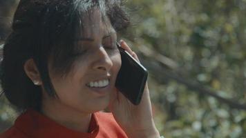 femme debout devant un arbre appelant avec un smartphone video