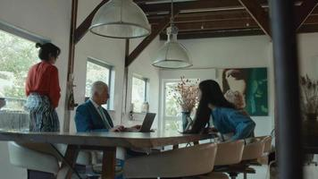 Woman and girl joining man and woman sitting at the table video