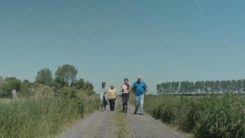 Two women a man and a girl walking and talking in the countryside video