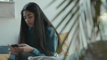 Girl sitting in corner of living room typing on smartphone video