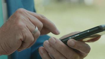 mani dell'uomo nell'area verde che digita sullo smartphone video