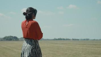 Woman standing in field calling with smartphone video