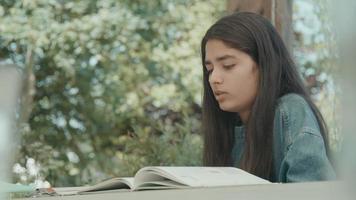 flicka sitter vid bordet i trädgården läser högt video